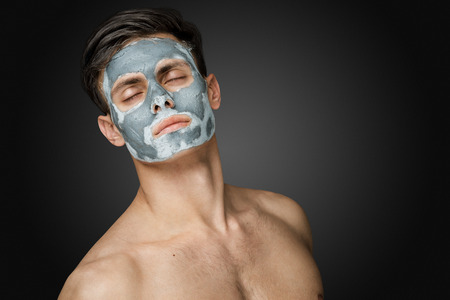 Portret van een mooie jonge man met een gezichtsbehandeling klei masker, gezicht en lichaam huidverzorging.
