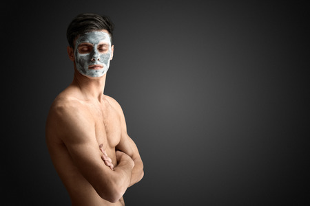 Portrait of a beautiful young man with a facial mud clay mask, face and body skin care treatment.