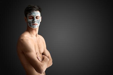 masaje facial: Retrato de un hombre joven con una m�scara de arcilla barro, la cara y el cuidado de la piel corporal tratamiento facial. Foto de archivo