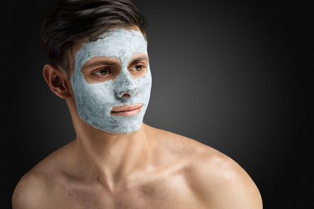 spas: Portrait of a beautiful relaxed young man with a facial mud clay mask, face and body skin care treatment. Stock Photo