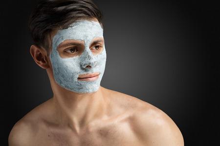 Portret van een mooie ontspannen jonge man met een gezichtsbehandeling modder klei masker, gezicht en lichaam huidverzorging.