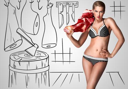 carnes rojas: Retrato creativo de una hermosa carnicero mujer sexy en bikini sosteniendo carne cruda en su hombro en vagos de una carnicería.