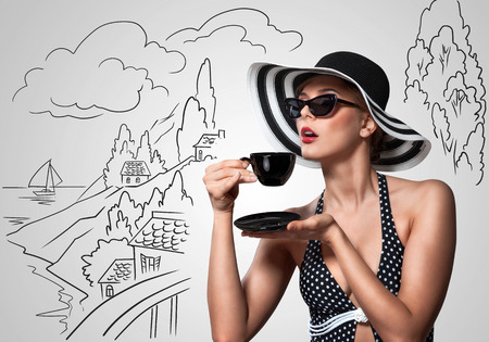 women: Creative vintage photo of a beautiful pin-up girl drinking tea on sketchy landscape .