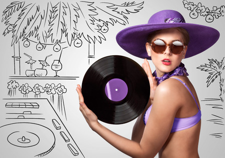 cocktail mixer: Colorful photo of a beautiful deejay in bikini holding a retro vinyl record in her hands on sketchy background of a DJ mixer and exotic landscape.