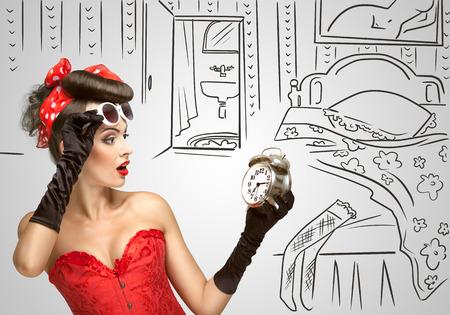 pin up vintage: Bella pinup ragazza in un vestito rosso d'epoca essendo tarda mattinata e in possesso di una sveglia retrò in mano su un abbozzato. Archivio Fotografico