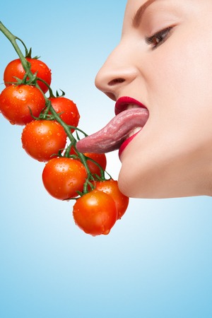 seductive women: Beautiful girl licking ripe red cherry tomatoes on the vine sexually with her seductive tongue on blue .