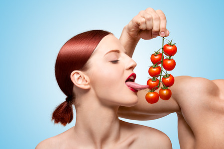 Beautiful girl licking ripe red cherry tomatoes on the vine sexually with her seductive tongue, foreplay with food and feeding on blue .