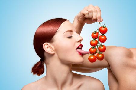 sexuel: Belle fille l�chant m�res tomates cerises rouges sur la vigne sexuellement avec sa langue s�duisante, les pr�liminaires avec de la nourriture et l'alimentation sur le bleu.