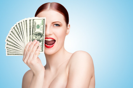 paper money: Creative portrait of a nude girl with beautiful face and body holding hand fan made of 100-dollar currency banknotes on blue background.