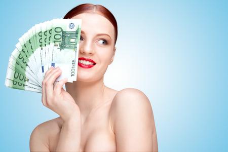 banconote euro: Ritratto creativo di una ragazza con bel viso e corpo azienda ventola fatta a mano di banconote in valuta 100 euro su blu.