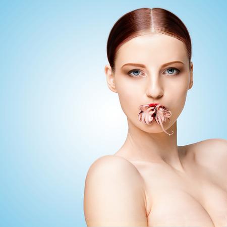 bebes ni�as: Retrato creativo de una ni�a con la cara hermosa y el cuerpo celebraci�n cocido el pulpo beb� en la boca en azul. Foto de archivo