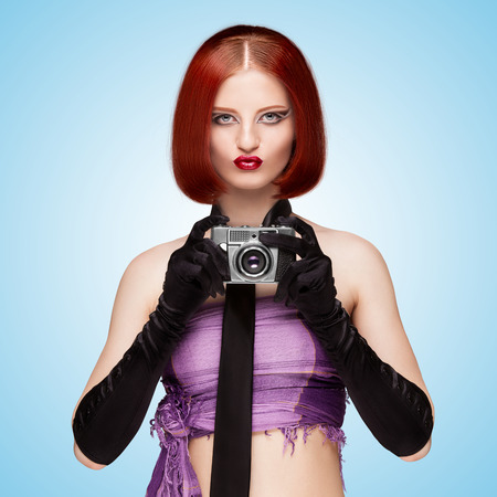 long gloves: Glamorous girl, vintage vamp style, dressed in a necktie and long gloves, shooting with an old vintage photo camera on blue .