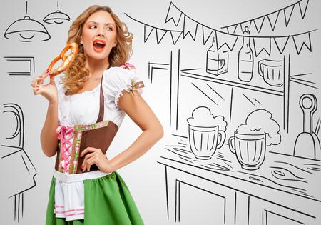 dirndl dress: Young sexy Oktoberfest woman wearing a traditional Bavarian dress dirndl eating a pretzel on sketchy bar counter . Stock Photo