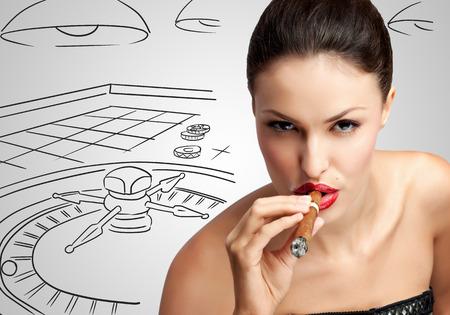 roulette: Ritratto di una donna ricca sexy, fumando un sigaro su abbozzato delle roulette del casinò. Archivio Fotografico