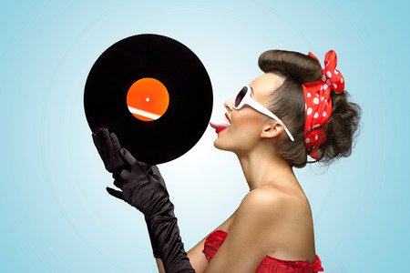 licking tongue: A photo of glamorous pin-up girl touching vinyl LP with tongue.