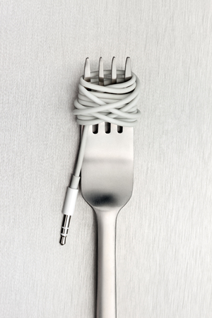 unhealthy thoughts: A shining fork with noodle made of cable with music jack plug in metal . Stock Photo