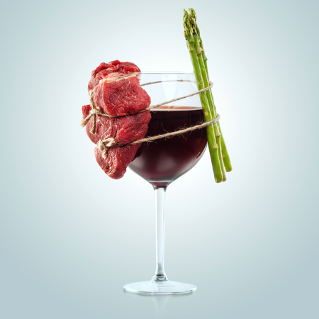pork meat: Interesting composition of meat and plants wiredly connected over the wine glass. Stock Photo