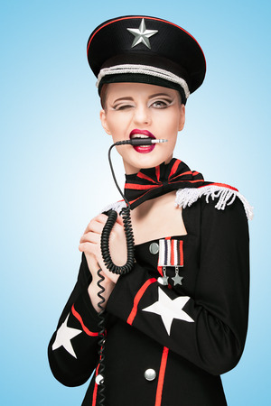 army girl: Sexy girl, dressed in a military uniform dress like a dominatrix, biting vintage unplugged music headphones on blue .