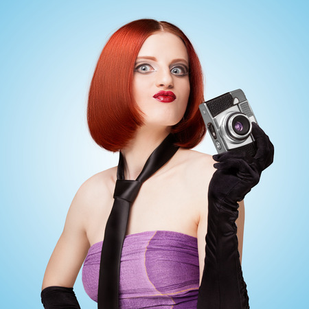 long gloves: Glamorous girl, retro vamp style, dressed in a necktie and long gloves, showing emotions and holding an old vintage photo camera on blue .