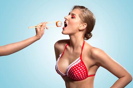 petite fille maillot de bain: Un r�tro photo cr�ative d'une jeune fille de pin-up en bikini manger des sushis de baguettes.