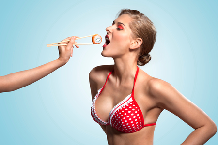 comidas: Una foto retro creativo de una joven chica pin-up en bikini comer sushi de palillos.