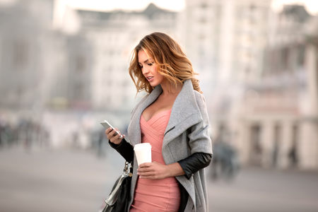 fashion girl style: A businesswoman checking email via mobile phone and holding a coffee cup against urban scene.