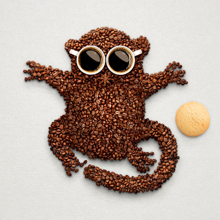 oatmeal cookie: A funny tarsier made of roasted coffee beans, two cups and star anise with an oatmeal cookie.