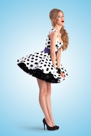 60s fashion: Creative vintage photo of a shy pin-up girl wearing a retro polka-dot dress. Stock Photo