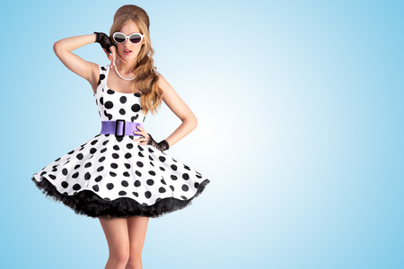 Vintage photo of a beautiful pin-up girl wearing a retro polka-dot dress and sunglasses, posing on blue background.