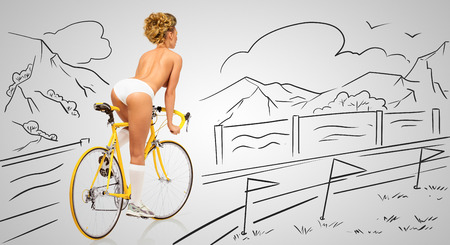 nude sport: Back view of a sexy pin-up female cyclist in white erotic panties riding a yellow racing bicycle on sketchy background of a race finish line.