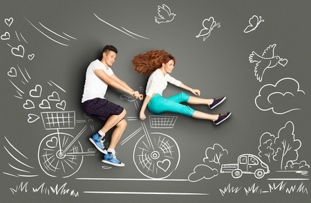 Happy valentines love story concept of a romantic couple on chalk drawings background of a countryside. Male riding his girlfriend in a front bicycle basket.