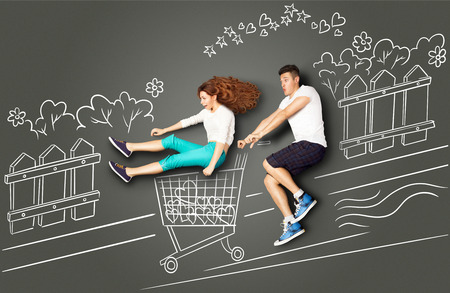 story: Happy valentines love story concept of a romantic couple on chalk drawings background. Male riding his girlfriend in a shopping cart along the street.