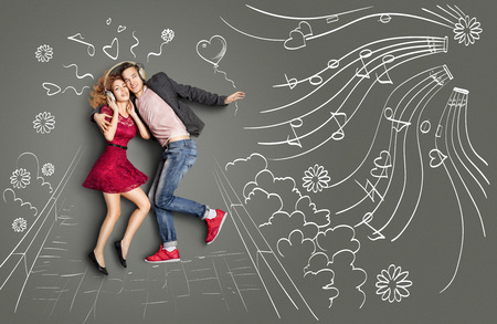 happy young man: Happy valentines love story concept of a romantic couple walking in the park, sharing headphones and listening to the music against chalk drawings background. Stock Photo