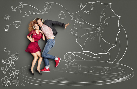 love story: Happy valentines love story concept of a romantic couple sharing headphones, listening to the music and dancing on a gramophone, against chalk drawings background. Stock Photo