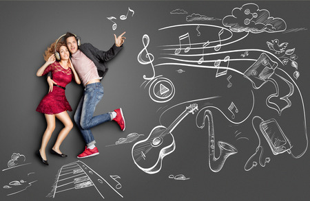 dating: Happy valentines love story concept of a romantic couple sharing headphones and listening to the music against chalk drawings background of musical instruments.