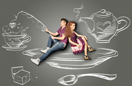 Happy valentines love story concept of a romantic couple sitting on a saucer and fishing in a teacup against chalk drawings background.