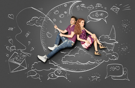 Happy valentines love story concept of a romantic couple fishing on a moon with a paper letter on a hook against chalk drawings background.