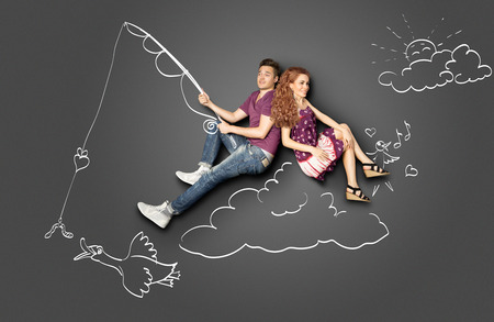 angling rod: Happy valentines love story concept of a romantic couple fishing on a cloud with a bait on a hook against chalk drawings background.