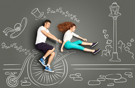 two story: Happy valentines love story concept of a romantic couple on chalk drawings background. Male riding his girlfriend on a vintage penny-farthing bicycle.