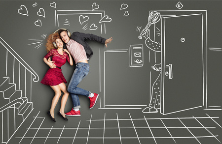neighbors: Happy valentines love story concept of a romantic couple sharing headphones and listening to the music on the stairs too loud for neighbors, against chalk drawings background. Stock Photo