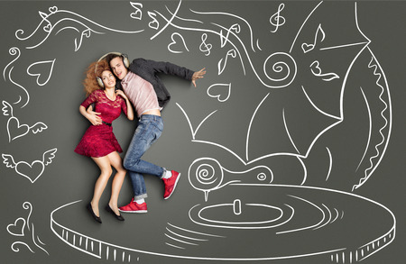 Happy valentines love story concept of a romantic couple sharing headphones, listening to the music and dancing on a gramophone, against chalk drawings background. photo