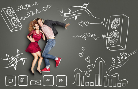 Happy valentines love story concept of a romantic couple sharing headphones and listening to the music against chalk drawings background of acoustic system, equalizer and player icons.