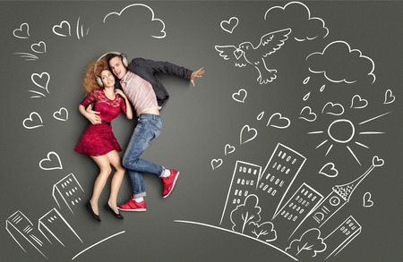Happy valentines love story concept of a romantic couple sharing headphones and listening to the music against chalk drawings urban background. Foto de archivo
