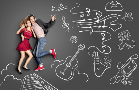 Happy valentines love story concept of a romantic couple sharing headphones and listening to the music against chalk drawings background of musical instruments.