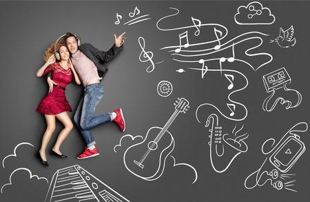 幸せなバレンタイン ヘッドフォンの共有と楽器のチョーク図面の背景音楽を聴いてロマンチックなカップルの物語のコンセプトが大好きです。