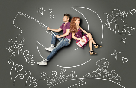 Happy valentines love story concept of a romantic couple fishing on a moon with a star on a hook against chalk drawings background of a night sky and a Cupid.