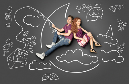 two story: Happy valentines love story concept of a romantic couple fishing on a moon with a paper letter on a hook against chalk drawings background.