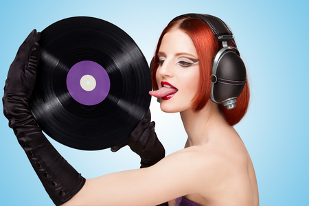 tongue and groove: Colorful photo of a sexy girl, wearing huge vintage music headphones and licking a purple LP microgroove vinyl record on blue background. Stock Photo