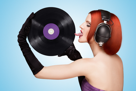 lp: Colorful photo of a seductive girl, wearing huge vintage music headphones and licking a purple LP microgroove vinyl record on blue background.
