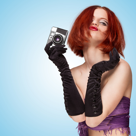 long gloves: Glamorous posing girl, wearing long gloves, holding an old vintage photo camera and grimacing on blue background.